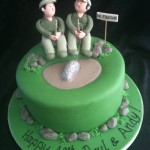 two men sat on rocks in matching outfits fishing. cake is iced green with sugar rocks going around the base of the cake