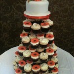 A tower of cupcakes with alternate orange gerberas and white roses with a top cutting tier with a posy of orange gerberas and roses
