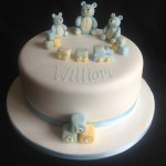 3 Blue teddies sat on a round cake with a train and building blocks