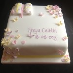 a square white cake with scattered pink, yellow and lilac flowers and butterflies with a bible in the top left corner