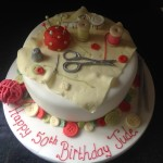 A round cake covered with buttons, cotton reels, scissors and pin cushion.
