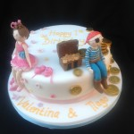 a round cake with a ballerina and pirate sitting ont he side with flowers and chocolate coins