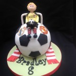 a ball cake featuring a goal keeper and goal sitting on top