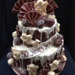 a 2 tiered cake covered in milk chocolate and white chocolate drizzle with fans and cherubs with scattered truffles