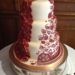 A 3 tiered stacked ivory sprayed gold cake. Left side has a ruby red drape in icing with gold pattern on and right side of cake is a replica of the Bride's henna patter in matching red colour, covered over all 3 tiers