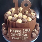 a round cake covered in milk chocolate bars with truffles on top and a big chocoalte 18
