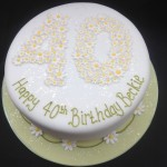 a round white iced cake on a pale green iced board with a 40 on top made from daisies with a daisy chain around the base