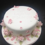 a round cake iced white with pink peonies around the base and green leaves, little flowers and pink butterflies scattered over the cake with christening message in the centre