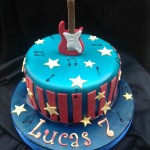 a bright blue cake with red stripes around the sides and a red electric guitar stood on top with yellow stars and black musical notes scattered over the cake