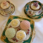 a selection of vintage decorated cupcakes on vintage plates and in vintage cups and saucers. decorated with lilac rose buds, pink rose buds, quitlted green and pink pattern and gold flowers