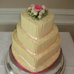 a 3 tiered stacked white chocolate cake with fresh pink roses on top tier and pink ribbon around base of each cake