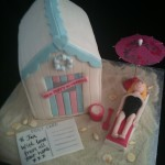 a Beach hut in white and pastel trim colours with a lady on a sun lounger and post card with Birthday message