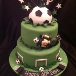A two tier round stacked cake covered green with goals around the base cake and footballs and a goal keeper around the edge of the top tier and a giant football on top. Stars bursting out of the cake on wires