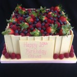 a square white chocolate coated cake with a selction of berries piled on top and raspberries around the edge of cake