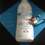 a Grey Goose vodka bottle on blue iced board and man draped over side of bottle