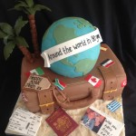 A chocolate brown suit cakes with round globe cake on top, palm trees, flags, passport and tickets to represent travel