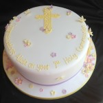 a round cake for a christening with piped yellow cross and little blossom flowers in pastel colours
