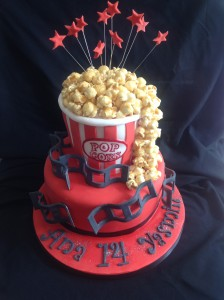 A two tiered cake round base in red with black film over cake. Top tier as a pop corn bucket with real pop corn spilling over