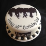 a round cake with sillouette of the Beatles on top and black and white balls arond base of cake