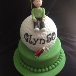 a green round iced cake with giant cake golf ball on top. figure sat on top of ball with a golf bag on the green tier