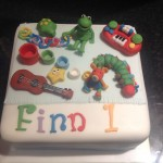 square cake with childs favourite toys on in various colours
