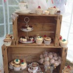a display of cupcakes, miniature cupcakes, brownies and cake pops displayed on crates and in tea cups