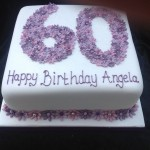 a square iced white cake with a 60 on top made from lilac, blue and purple cut blossom flowers and a row of flowers around the base of the cake