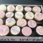a selection of iced cupcakes in pink and cream with bunting, bunnies, quilted design and flowers in the shape of hearts