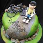 a green sprayed cake with rocks around the base. A path leading over the cake with a bike laying against some rocks on top of the cake and a man dressed in bike gear sat next to it
