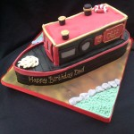 a cake in the shape of a Barge boat on water. base of boat is black with green body and red roof, doors and gold trim