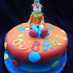 a round airbrushed cake with contrasting colours from blue to red and orange with a colourful clown sat on top of the cake